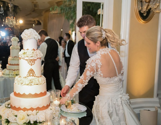 Bride in marchesa couture wedding dress groom in vest cutting wedding cake white rose gold flowers
