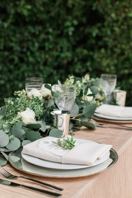Garden wedding reception table with greenery runner, white roses, golden tablecloth, charger