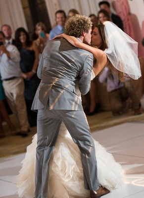Groom dipping and kissing bride on dance floor