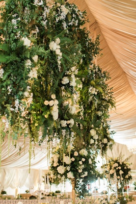 Wedding reception champagne gold tent with chandeliers and flowers greenery white gold green decor