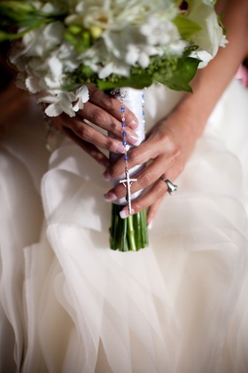 Bride holds white and green bouquet with blue bead rosary