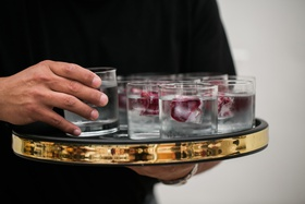 gold border serving platter with water glasses with flower petals in ice cubs