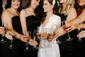 bride in white robe dressing gown headpiece black bridesmaid dresses champagne cheers getting ready