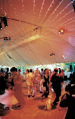 Guests dance at tented reception with string lights