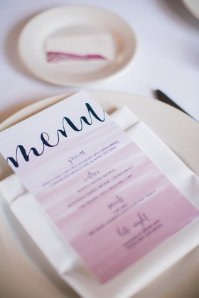 small reception menu with calligraphy and an ombré design in pink