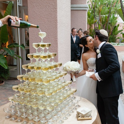 Champagne tower with coupe glasses bride in Monique Lhuillier dress kisses groom in yarmulke