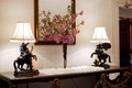 Horse lamps next to white seating cards and pink flowers