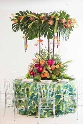 tropical wedding inspiration, tropical print linens, arrangement of split leaves overheard