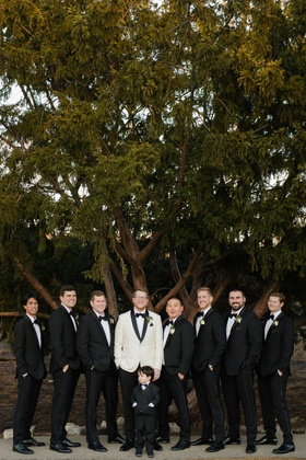 wedding portrait groom in white tuxedo jacket groomsmen in black white tuxedo suits ring bearer