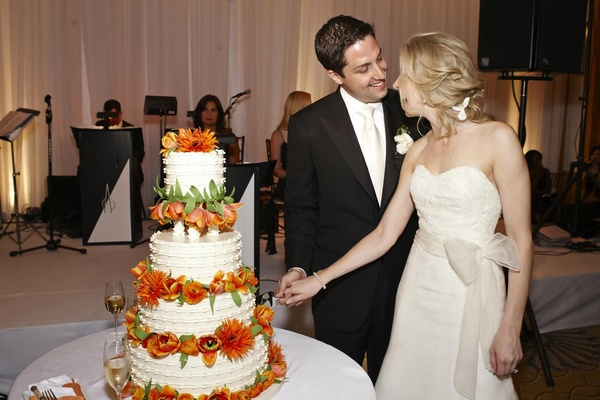 Bride and groom cut white cake with orange flowers
