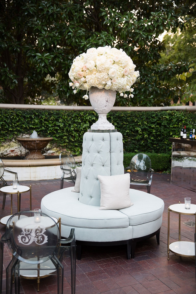 Flower arrangement on top of round settee tufted pillow monogram on ghost chairs side tables candles