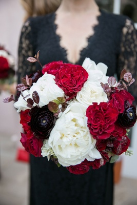 Bridesmaid in v-neck black lace bridesmaid dress holding white, red, black bouquet rose peony