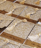 Gold patterned escort cards with tassels