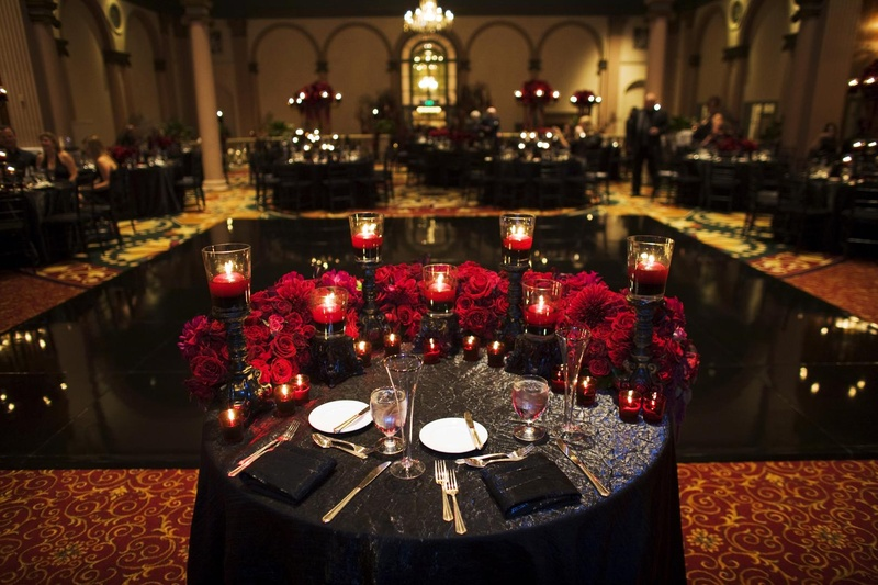 Wedding reception sweetheart table with black linens, red roses, and black candleholders