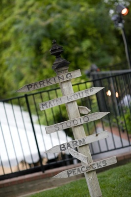 Wood sign with directional arrows at wedding