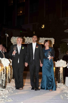 Orthodox Jewish groom and parents on aisle