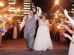 Wedding reception grand exit bride and groom hold hands sparkler wand exit friends and family city