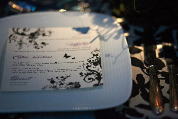menu card on white plate, with green and purple floral design