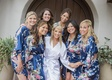 bride in white satin bridal gown, bridesmaids in blue floral bridesmaids gowns