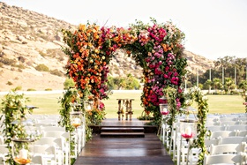 outdoor wedding reception dark wood aisle with white chairs greenery pink orange yellow flowers
