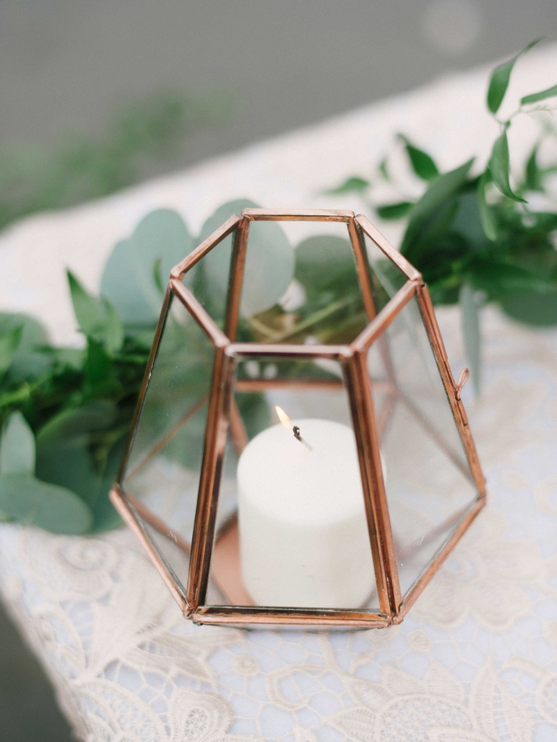 small white candle in mirrored geometric terrarium on white lace table linen with greenery