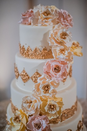 White wedding cake with golden embellishments, yellow, pink, white sugar flowers