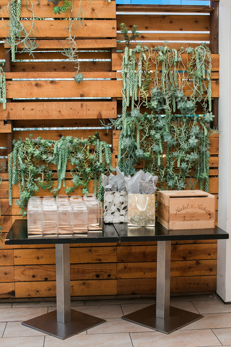 bridal shower guest table in front of wood pallet wall with succulents dripping down