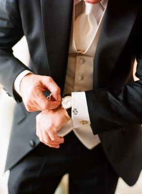 Groom in a black tuxedo, white satin vest and tie