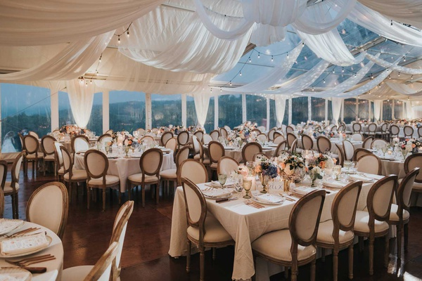 tent wedding with french oval chairs drapery patio lights low centerpieces