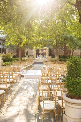 gold white cushions rose aisle low hanged branches trees dallas texas flower arch