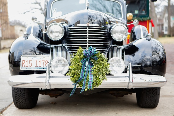 Green wreath with blue bow on front grill of black classic Cadillac car