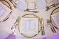 white tablescape gilt rimmed chargers indian hindu wedding california purple lighting napkin
