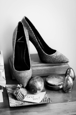 Black and white photo of bride's sparkly heels on wood stand, Love You! note