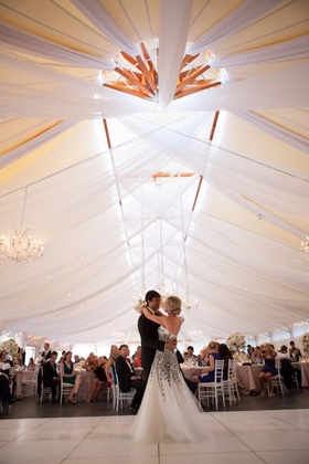Bride and groom dance under draped reception tent