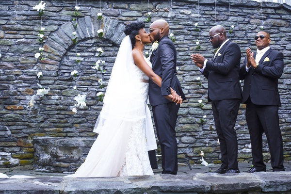 bride in eddy k, groom in charcoal suit, stone wall backdrop with strings of flowers