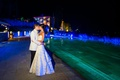 Bride in a strapless Vera Wang gown with champagne bands kisses groom in tuxedo with white coat