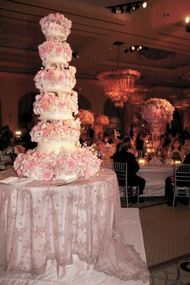 five tier white cake covered in realistic pink sugar flowers