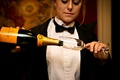 Server in black bow tie pouring Veuve Clicquot champagne into champagne flute glass