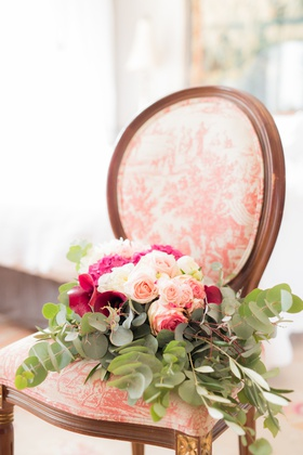 wedding bouquet on top of upholstered vintage antique wood chair greenery with pink and white flower