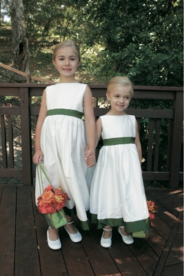 Flower girls in white dresses with green baskets