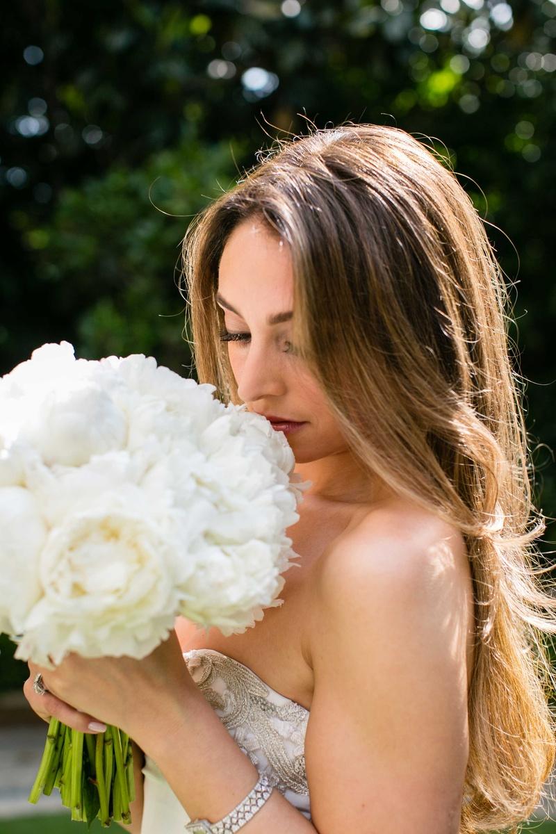 Bride with long hair and strapless Oscar de la Renta wedding dress sniffs white peony bridal bouquet