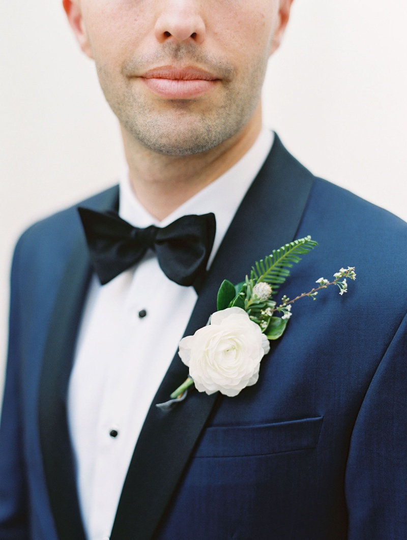 groom with navy tuxedo jacket black lapels white ranunculus flower fern greenery boutonniere