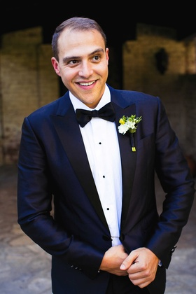 a groom smiling in a dark blue tuxedo and black bow tie with green and white boutonniere