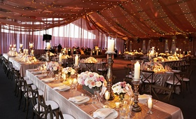 Wedding reception under drapery and string lights with rustic touches