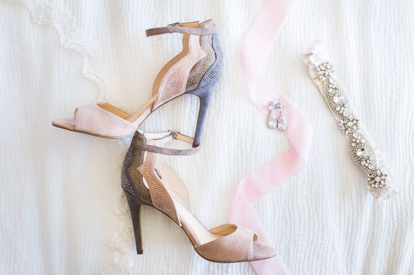 gray pink bridal heels by jessica simpson garter crystals ribbon on white bed sheet pre wedding