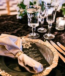 Wedding reception black linens table gold rim glassware and charger black gold menu card calligraphy