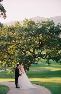 Bride and groom kiss under tree at Ojai Valley Inn & Spa