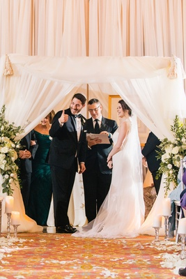bride in lela rose wedding dress, groom in michael kors tuxedo, thumbs up at Jewish ceremony