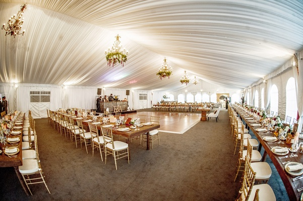 wedding reception space with gold chiavari chairs and white drapery ceiling