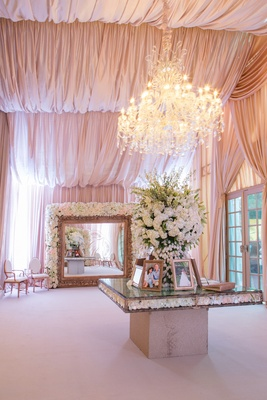 Guest book table under chandelier and large mirror